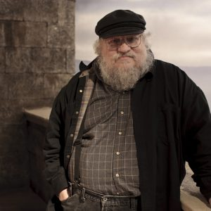 "In this publicity image released by HBO, author George R.R. Martin whose novel series have been adapted into the HBO series ""Game of Thrones,"" is shown on the set. (AP Photo/HBO, Nick Briggs )"